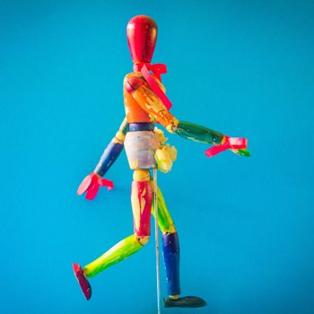 Essere creativi: abbi cura di te. Un manichino variopinto nell'atto di camminare